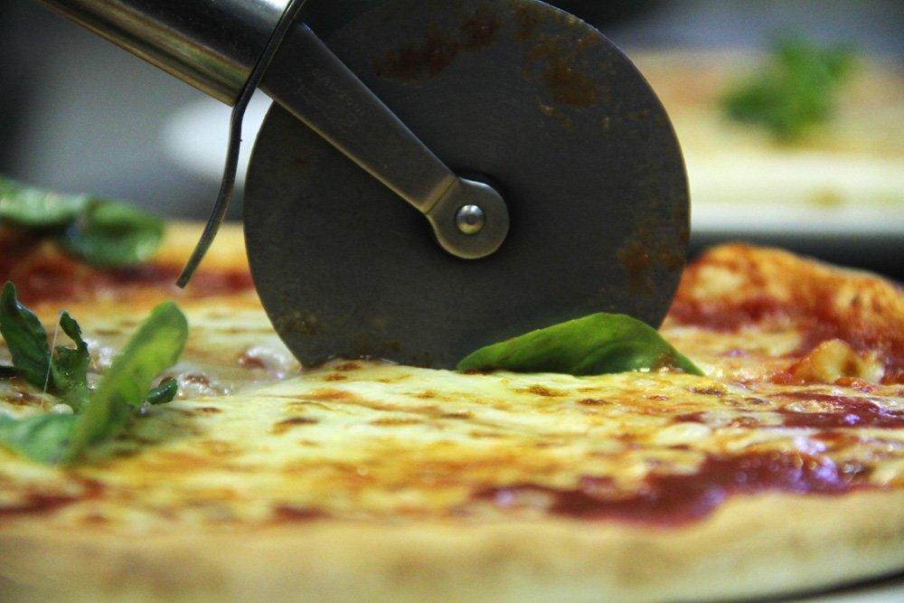 pizza che sta per essere tagliata